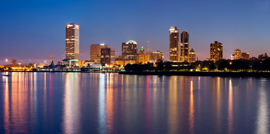 Image of Milwaukee skyline at twilight with city reflection in lake Michigan.